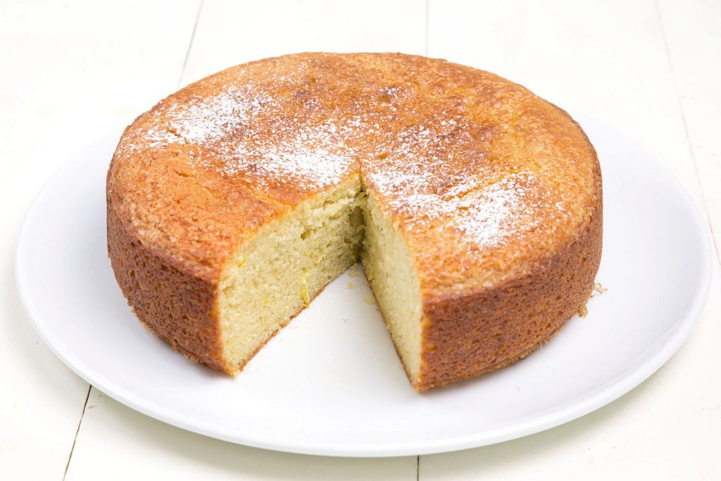 Olive Oil Yogurt Cake With Slice Taken Out On A White Serving Platter