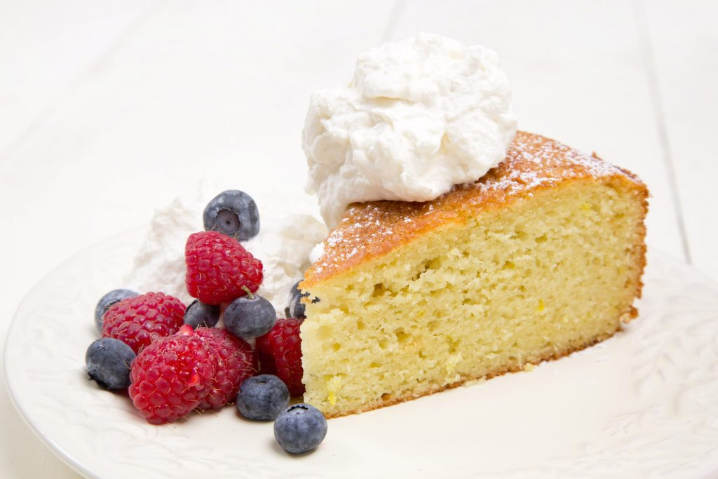 slice of orange olive oil cake with berries and whipped cream on a white plate