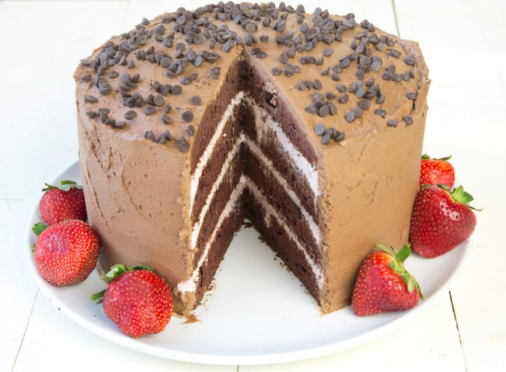whole 4 layer chocolate cake with strawberry mousse between the layers with chocolate frosting and chocolate chips on the top, with a slice cut out sitting on a white plate with a strawberries around the plate
