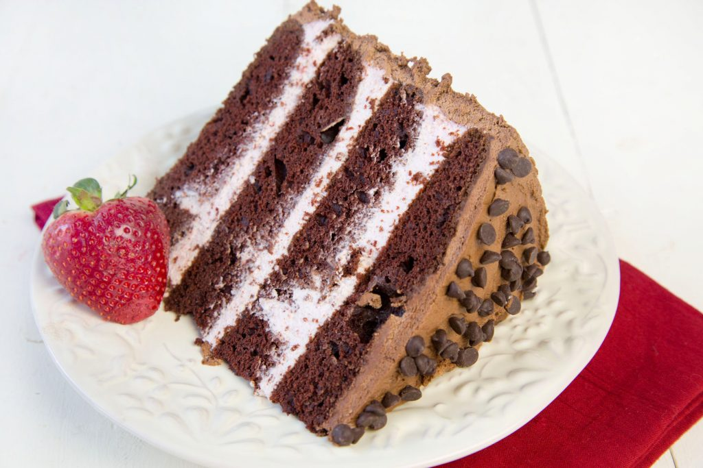 slice of 4 layer chocolate cake with strawberry mousse between the layers with chocolate frosting and chocolate chips on the top sitting on a white plate with a strawberry on the plate and a red napkin under the plate on a white table