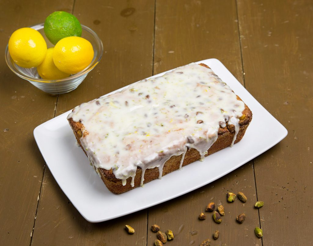 Meyer Lemon Pistachio Pound Cake with a lemon lime glaze on a white plate on a brown table with a bowl of lemons and limes and sprinkled pistachios