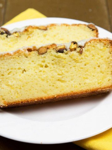 2 slices of a lemon pound cake sitting on a white plate on top of a yellow napkin on a brown table