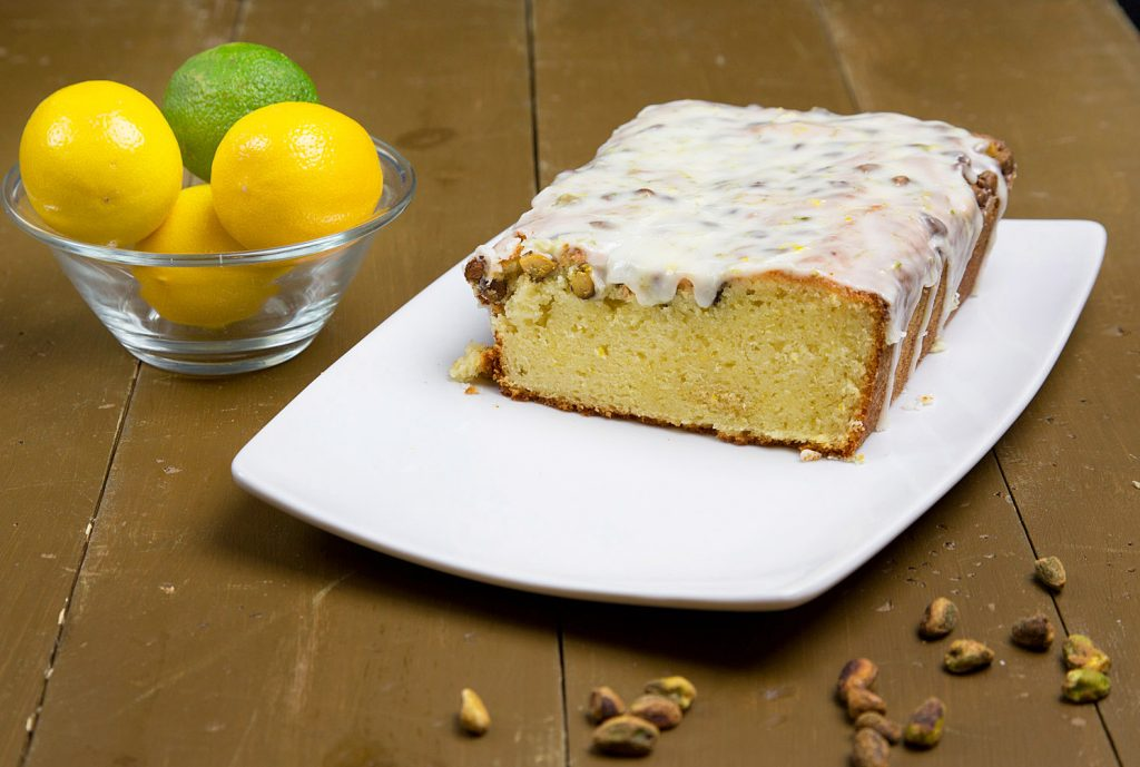 side view of sliced Meyer Lemon Pistachio Pound Cake with a lemon lime glaze on a white plate on a brown table with a bowl of lemons and limes