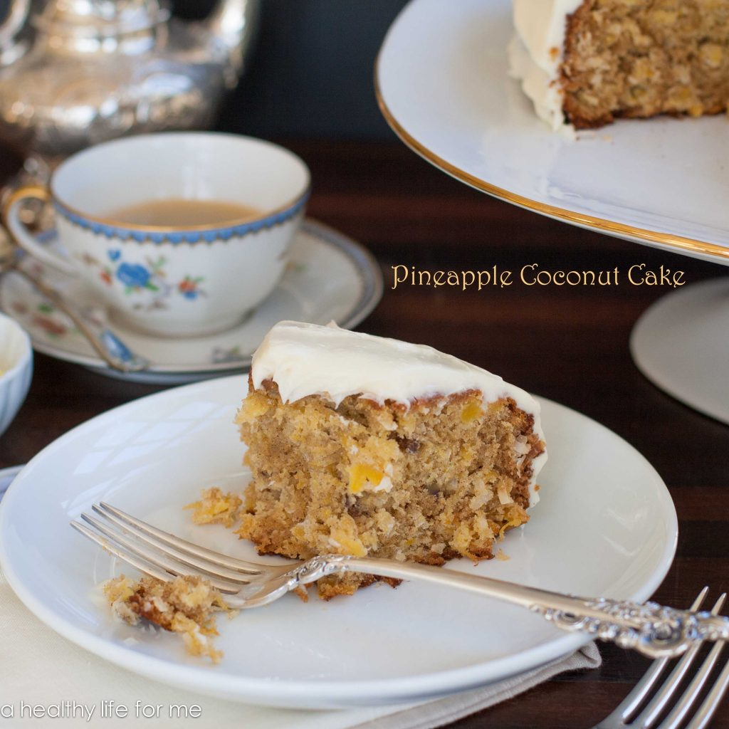Pineapple coconut cake with a piece missing sitting on a white plate with a fork, and a coffee cup in the back ground