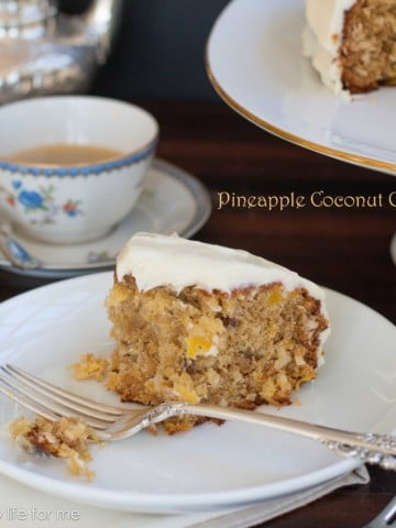 half-eaten slice of pineapple coconut cake on a white plate with a fork and teacup in the background