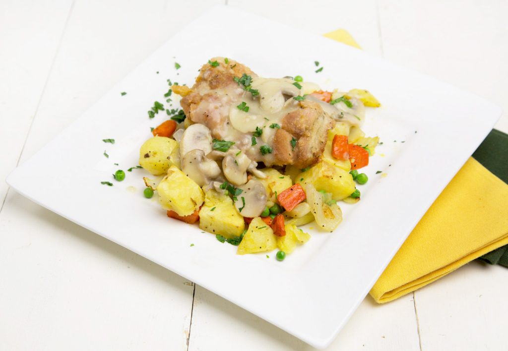 Chicken on a bed of potatoes, carrots, peas and other vegetables topped with mushroom sauce on a white plate with a yellow napkin on the side