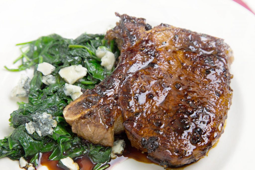 Balsamic Glazed Pork Chop sitting on a white plate with a side of greens with gorgonzola cheese crumbles