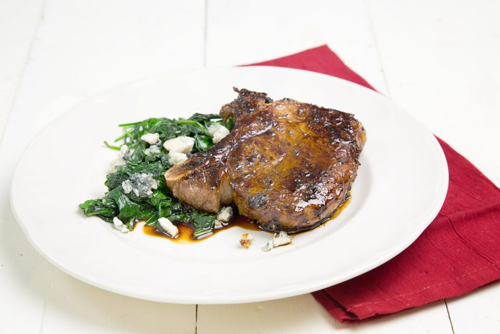 Balsamic Glazed Pork Chop sitting on a white plate on a white table with a side of greens and a red napkin under it