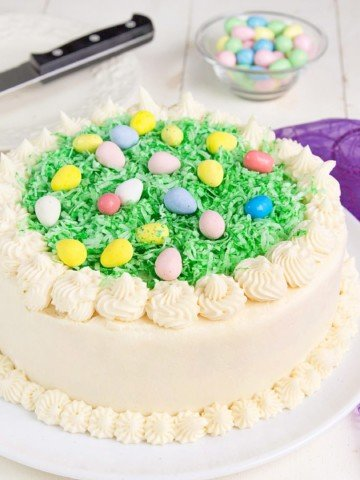 decorated Easter Cake on a white platter with a purple napkin on the side