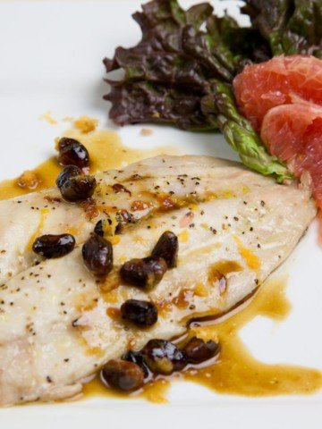 roasted pompano with sauce and pistachios on a white plate with grapefruit slice garnish