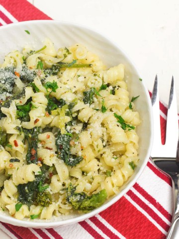 white bowl of pasta aglio olio with broccoli rabe on a red and white napkin