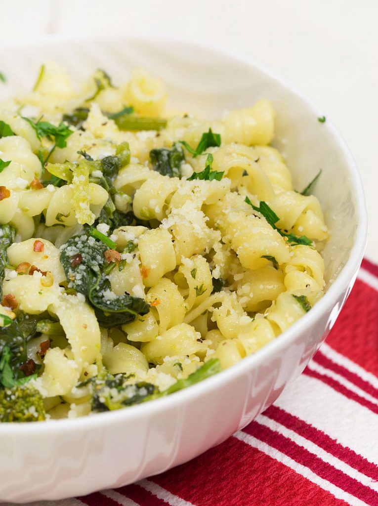 pasta with brocolli rabe and olive oil in a white bowl sitting on a red striped napkin