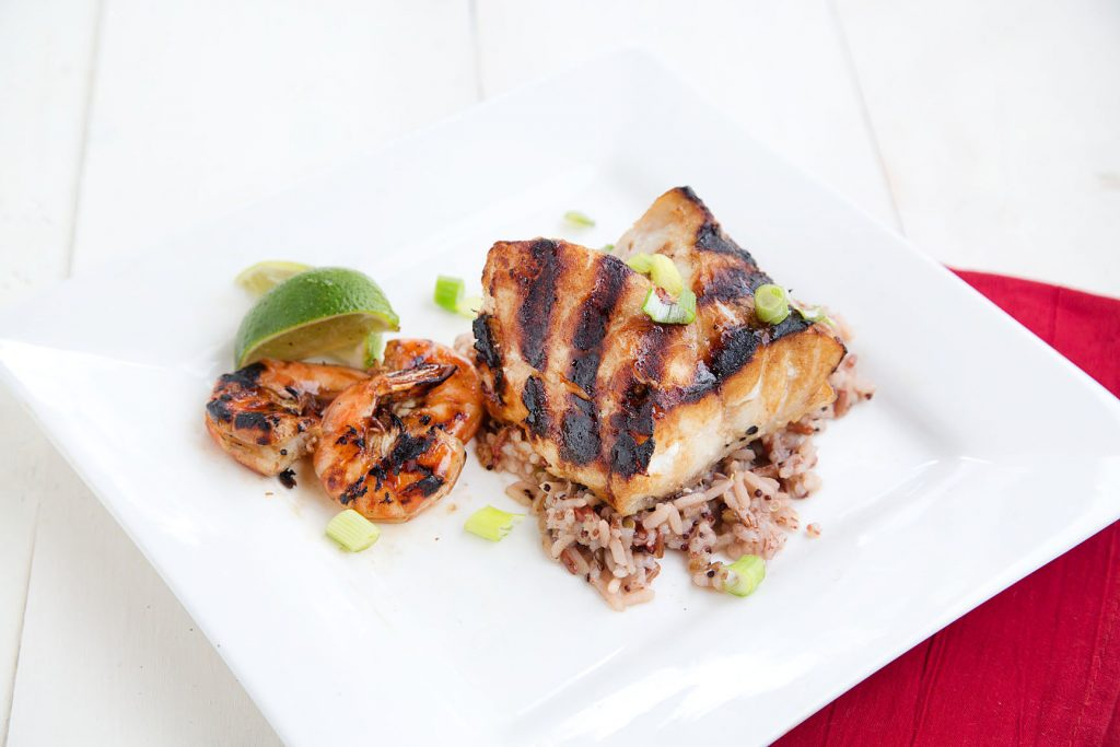 Grilled Alaskan Rockfish on wild rice with grilled shrimp sitting on a square white plate with lime wedges as garnish. This is on a white table with a red napkin under the plate