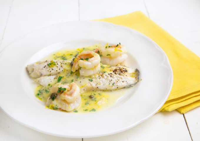 black seas bass topped with shrimp in a lemon caper sauce on a white plate