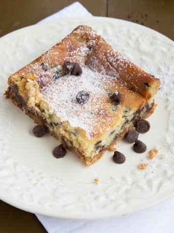 square slice of chocolate chip cheesecake bar on a white plate