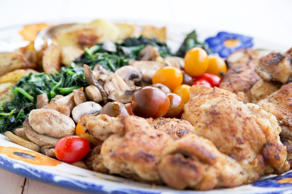 side view of Seared Chicken with fried potatoes, sauteed spinach, mushrooms and heirloom grape tomatoes