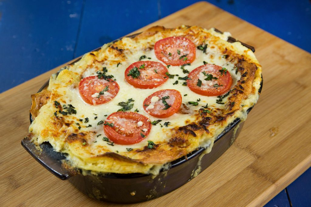 baking dish of cooked Spinach and Tomato Lasagna on a wooden cutting board