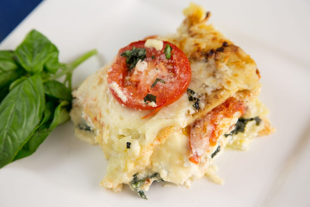 portion of Spinach and Tomato Lasagna on a white plate with basil sprigs on the side