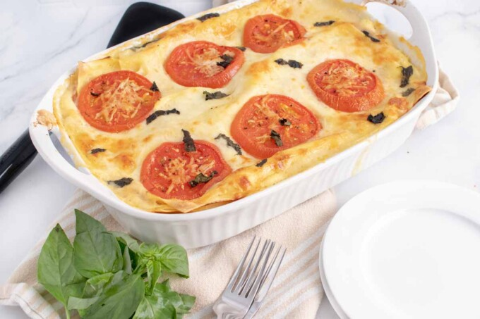 pan of baked lasagna with white plates and basil in the foregroung
