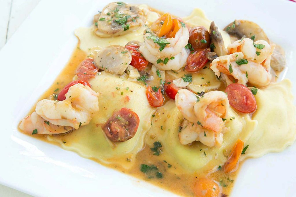 ravioli topped with shrimp in a scampi sauce served on a white plate