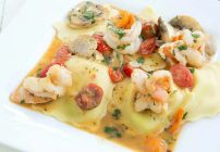 Ricotta and spinach ravioli topped with shrimp in a scampi sauce