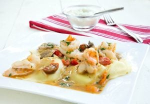 Spinach and cheese ravioli topped with shrimp in a garlic scampi sauce
