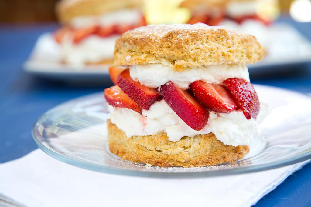 side view of individual strawberry shortcake on a clear glass plate