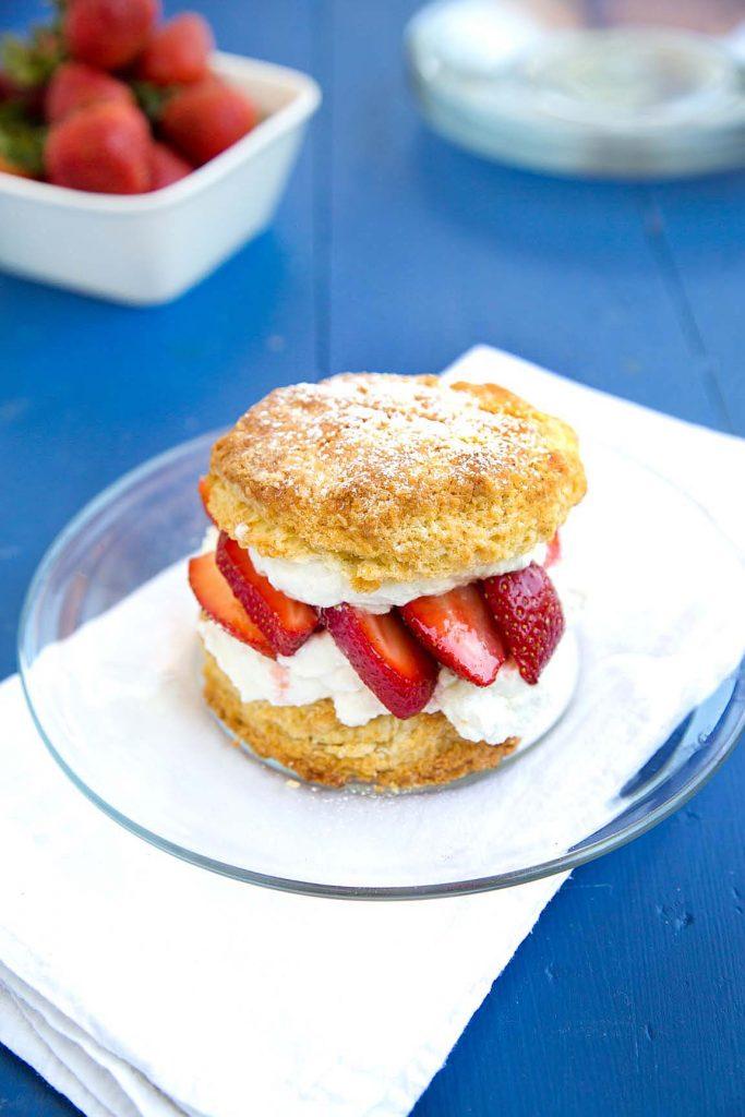 individual strawberry shortcake scone on a glass plate on a white napkin