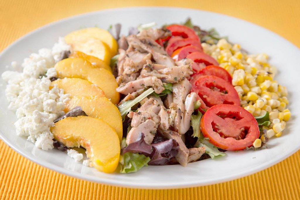 salad of feta cheese, sliced peaches, grilled chicken, sliced tomatoes and corn on a white plate