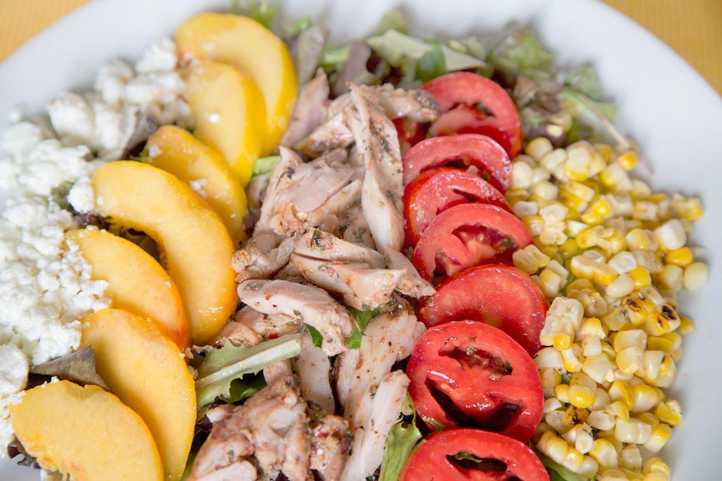 partial overhead view of a salad of feta cheese, sliced peaches, grilled chicken, sliced tomatoes and corn on a white plate