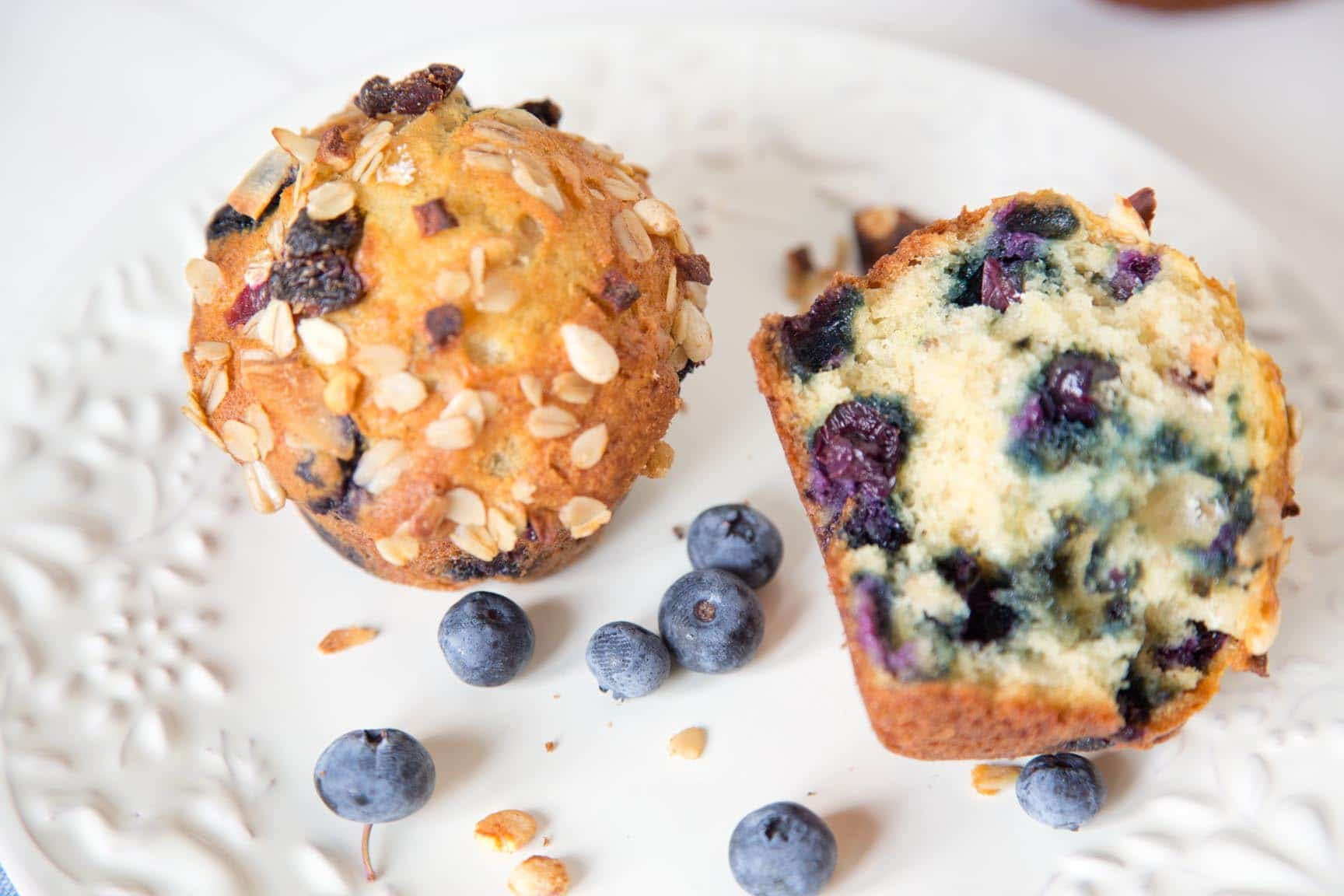 one  and one half Blueberry muesli muffins on a white plate with blueberries