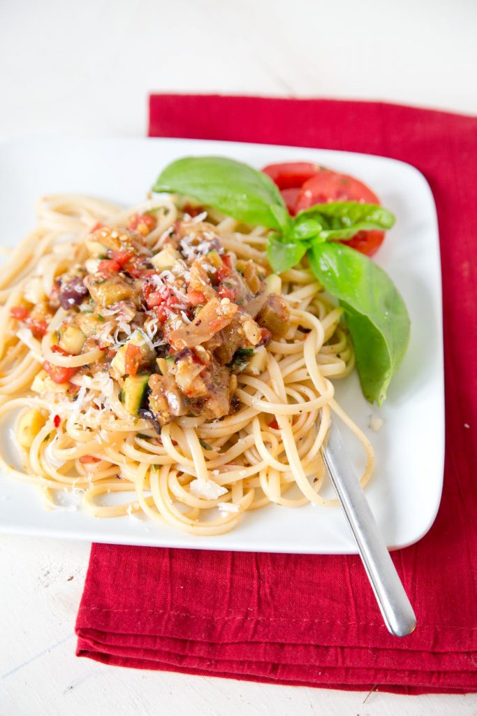 Pasta with vegetables on a white plate with a sprig of basil and a fork, sitting on a red napkin