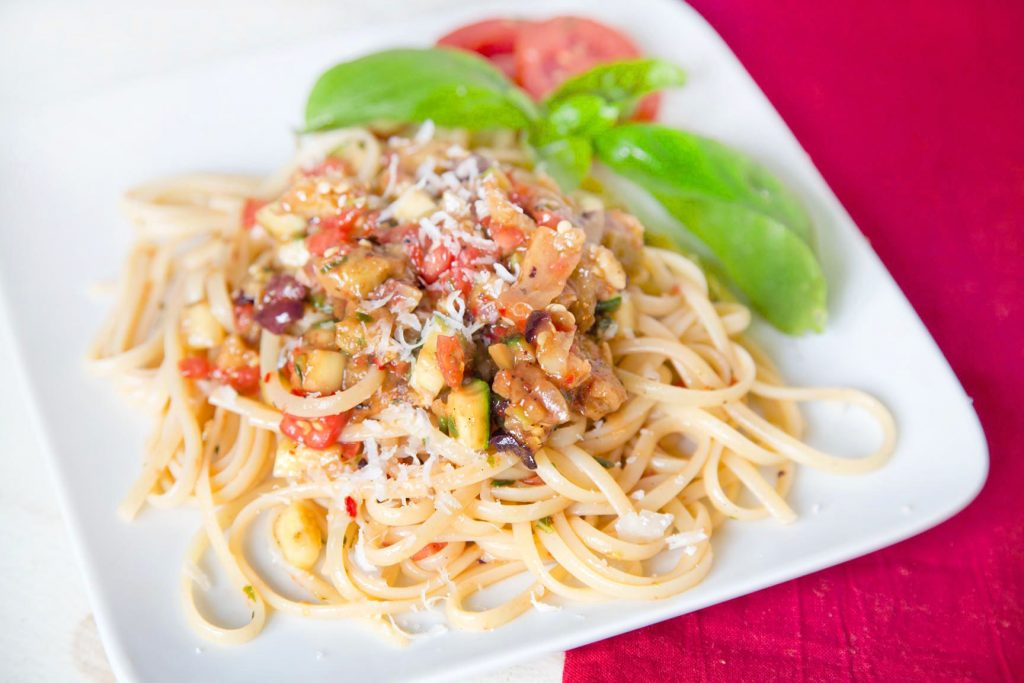 Pasta with vegetables and a sprig of basil on a white plate on a red napkin