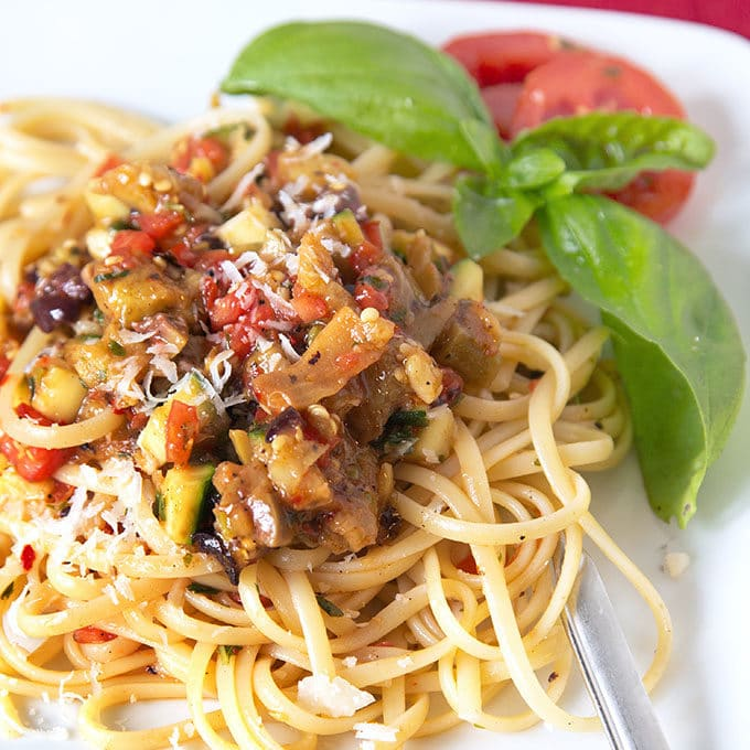 pasta topped with vegetables on a white plate with a sprig of basil