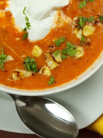 partial view of a white bowl of roasted pepper soup on a white plate with a spoon