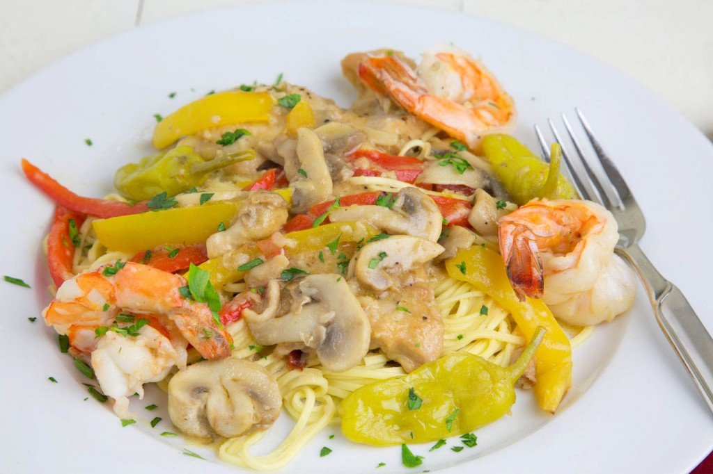 Gulf Shrimp, Chicken tenders , tuscan peppers and mushrooms served over pasta on a white plate with a fork