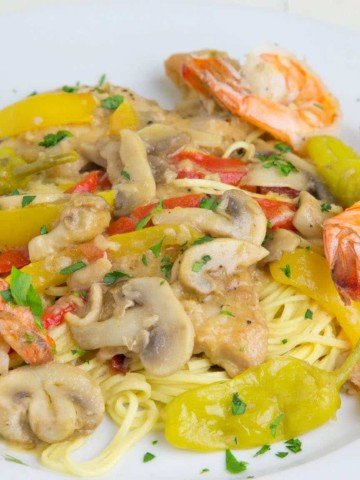 chicken and shrimp Toscano over pasta on a white plate