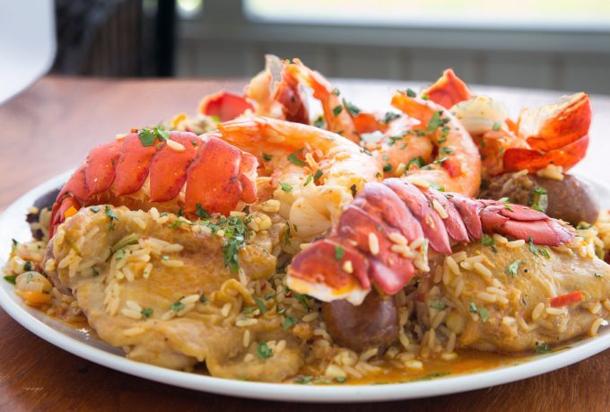 side view of Tex-Mex Jambalaya with split lobster tails on a white platter