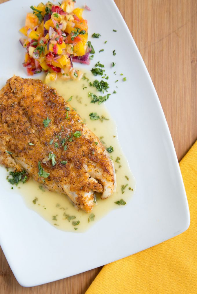 overhead view of cajun style snapper with a lime margarita sauce, fruit salsa and garnished with chopped parsley on a white plate