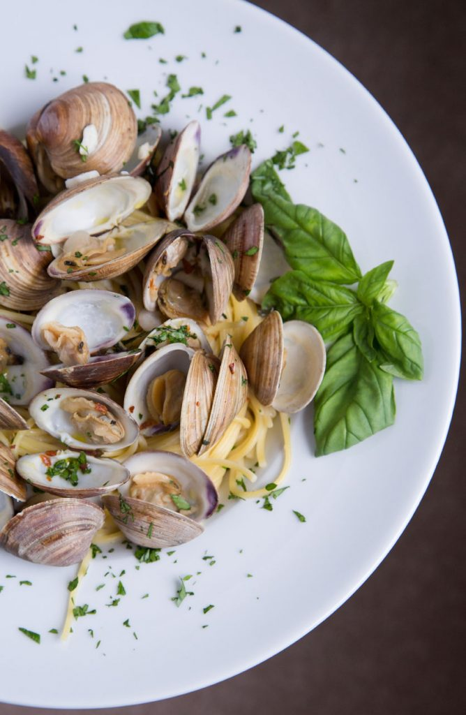 partial shot of Clams and Spaghetti in a white bowl with a sprig of basil on the side
