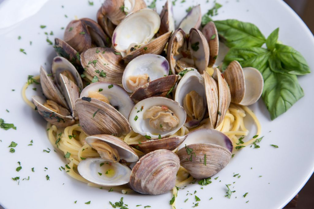 whole cooked Clams and Spaghetti in a white bowl with a sprig of basil