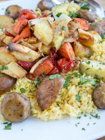 White platter with saffron rice and root vegetables made paella st yle on a wooden cutting board