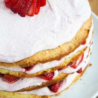 partial view of a strawberry cream cake on a white platter