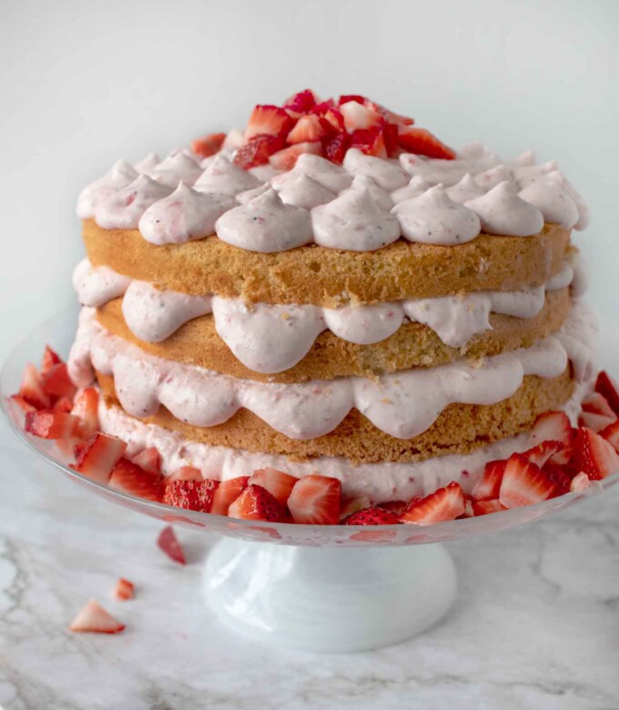 side view of completed Italian strawberries and cream cake on a cake pedestal