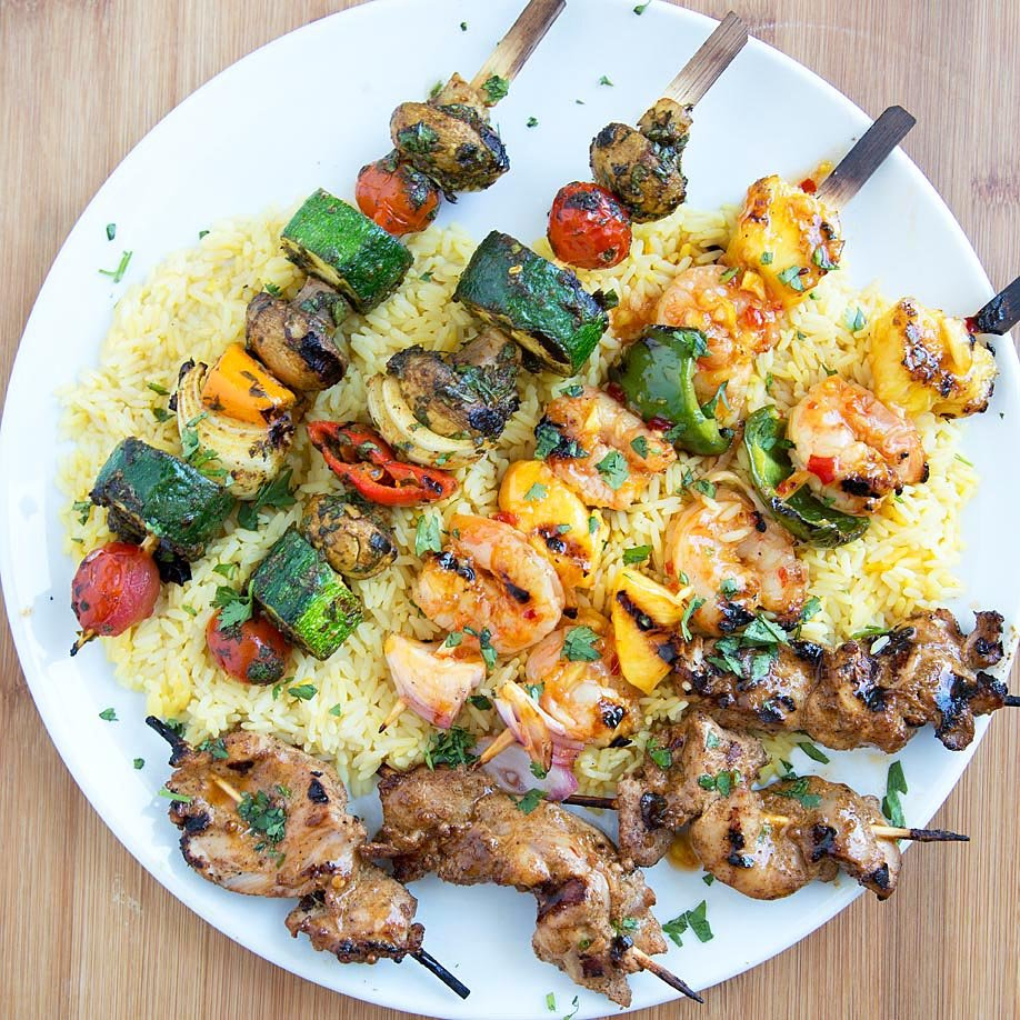 Moroccan Vegetable Skewers, Sweet and Spicy Shrimp Skewers and tandoori chicken skewers on a bed of rice on a white plate on top of a cutting board