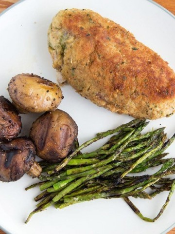 overhead view of cooked breaded stuffed pork  with grilled mushrooms and asparagus on a white plate