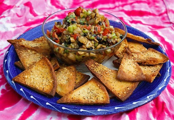 glass bowl of caponata with pita toasts on a blue rimmed plate