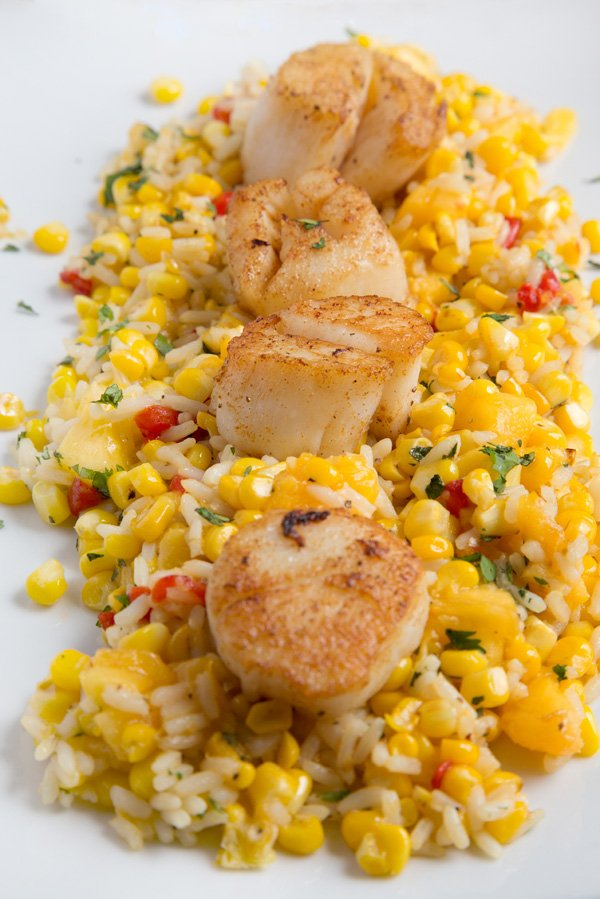 three pan seared scallops on a bed of rice and sweet corn on a white platter