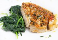 A close up of a white plate with ginger-garlic swordfish and sauteed spinach