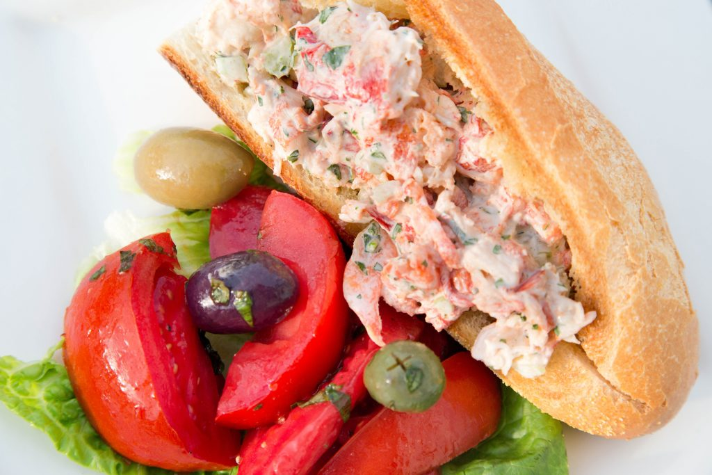 lobster salad on long roll with a tomato and olive salad on a white plate
